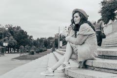 il ritratto una bella ragazza in un cappello, si siede sui residui tiene i capelli dal vento Passeggiata intorno alla città ritra fotografia stock libera da diritti