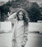 il ritratto una bella ragazza in un cappello, si siede sui residui tiene i capelli dal vento Passeggiata intorno alla città ritra immagine stock