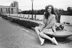 il ritratto una bella ragazza in un cappello, si siede sui residui tiene i capelli dal vento Passeggiata intorno alla città ritra fotografia stock