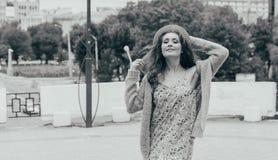 il ritratto una bella ragazza in un cappello, si siede sui residui tiene i capelli dal vento Passeggiata intorno alla città ritra immagini stock libere da diritti