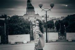 il ritratto una bella ragazza in un cappello, si siede sui residui tiene i capelli dal vento Passeggiata intorno alla città ritra fotografie stock libere da diritti