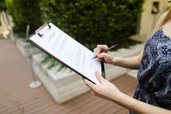 Il ritratto vicino della donna firma il contratto su fondo di costruzione Fotografia Stock
