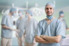 Il riuscito chirurgo sta sorridendo Molti chirurghi nel fondo Fotografia Stock Libera da Diritti