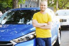 Il riuscito giovane felice e la sua automobile nel tramonto morbido si accendono su fondo urbanistico Uomo di affari con il veico immagini stock libere da diritti