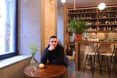 Il riuscito giovane, ospite del café sorride e esamina la macchina fotografica Fotografie Stock Libere da Diritti