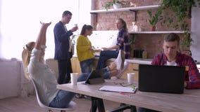 Il riuscito gruppo della gente dell'ufficio è mangiante e lavorante con le compresse ed i computer portatili in cucina durante la video d archivio