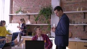 Il riuscito gruppo di giovani uomini d'affari è mangiante e lavorante con le compresse ed i computer portatili in cucina durante  stock footage