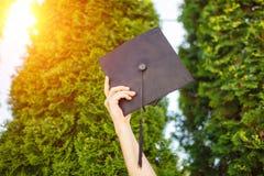 Il riuscito laureato, in vestiti accademici, ha sollevato sulla graduazione c fotografia stock libera da diritti
