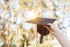 Il riuscito laureato, in vestiti accademici, ha sollevato sulla graduazione c immagini stock libere da diritti