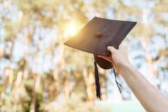 Il riuscito laureato, in vestiti accademici, ha sollevato sulla graduazione c fotografia stock