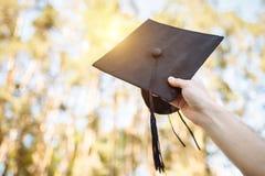 Il riuscito laureato, in vestiti accademici, ha sollevato sulla graduazione c immagine stock libera da diritti