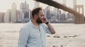 Il riuscito uomo d'affari europeo felice fa una telefonata sullo smartphone, parlante e sorridente vicino al ponte di Brooklyn 4K video d archivio