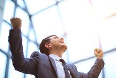 Il riuscito uomo d'affari felice alza le sue armi su che celebra la sua vittoria fotografia stock