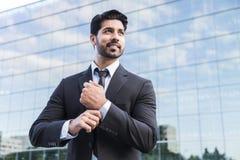Il riuscito uomo d'affari o lavoratore che sta nel vestito e raddrizza la camicia fotografie stock libere da diritti
