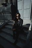 Il rivestimento d'uso del motociclista della bella donna orientale posa in cortile del condominio d'annata fotografie stock libere da diritti