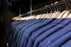 Il rivestimento della giacca sportiva sullo scaffale nei ganci di legno di modo degli uomini del deposito copre Immagine Stock