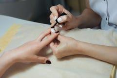 Il rivestimento trasparente dei chiodi è un primo piano nel salone di bellezza Processo del manicure? Le mani della femmina? Fotografie Stock