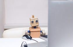 Il robot è occupato lavorare al computer alla tavola Fotografie Stock Libere da Diritti