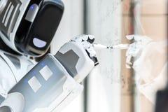 Il robot astuto sta stando contro il bordo trasparente Fotografia Stock
