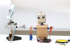 Il robot con le mani ed altre parti per il montaggio del robot sono sopra Immagine Stock