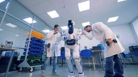 Il robot del controllo di due ingegneri e lo ripara stock footage