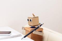 Il robot scrive con una penna a sfera alla tavola Immagini Stock Libere da Diritti