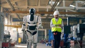 Il robot sta camminando lungo la fabbrica sotto controllo di uno specialista maschio archivi video