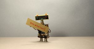 Il robot sta provando ad attirare l'attenzione e concentrarsi sull'importante Un robot abile del giocattolo che ondeggia la sua m stock footage