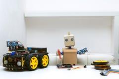 Il robot tiene in sue mani le parti per il montaggio del robot, Fotografie Stock Libere da Diritti