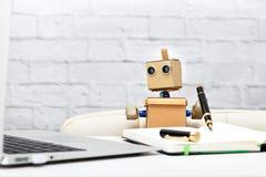 Il robot tiene una penna in sua mano, sedentesi ad una tavola Fotografia Stock