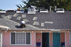 Il Roofer che sostituisce le mattonelle di tetto ad un rosa ha colorato il motel Immagini Stock Libere da Diritti