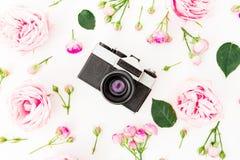 Il rosa è aumentato fiori con la vecchia retro macchina fotografica su fondo bianco Disposizione piana, vista superiore Concetto  fotografia stock