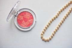 Il rosa della tavolozza arrossisce Make up arrossisce mosaico con la collana della perla su fondo bianco fotografie stock