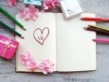 il rosa di concetto del fondo del biglietto di S. Valentino fiorisce sul taccuino bianco con i contenitori di regalo Fotografia Stock
