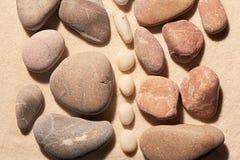 Il rosa e le pietre tonificate grige del mare hanno separato da bianco sulla sabbia Immagini Stock