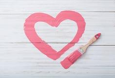 Il rosa ha dipinto il cuore su fondo di legno bianco fotografia stock libera da diritti