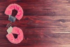 Il rosa lanuginoso ammanetta su una tavola di legno scura fotografia stock
