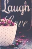 Il rosa punteggia la tazza di tè in pieno delle rose secche, stile d'annata Immagini Stock