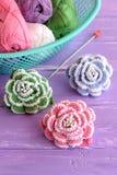 Il rosa, verde e blu lavora all'uncinetto i fiori decorati con le perle Matasse merce nel carrello, gancio e rose tricottate lumi immagine stock libera da diritti