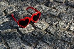 Il rosso, cuore ha modellato gli occhiali da sole su un pavimento sulla via del ciottolo immagini stock