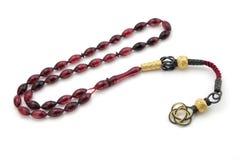 Il rosso del chiaretto ha colorato le perle del rosario con la nappa d'argento colorata oro isolata su bianco immagini stock