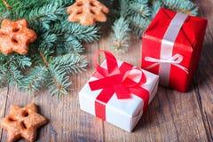 Il rosso ed il bianco presenta accanto ai biscotti e ad un ramo del pino su un fondo di legno Concetto di compera di Natale Fotografie Stock