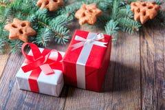Il rosso ed il bianco presenta accanto ai biscotti e ad un ramo del pino su un fondo di legno Concetto di compera di Natale Immagine Stock