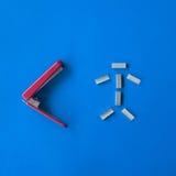 Il rosso ed il bianco hanno isolato lo strumento della cucitrice meccanica del metallo su fondo blu Immagine Stock