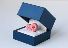 Il rosso ha sfrigolato cuore dentro un contenitore di gioielli blu Fotografie Stock Libere da Diritti