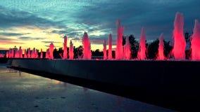 Il rosso moderno ha acceso le fontane del parco al tramonto recente Illuminazione architettonica del LED video 4K stock footage