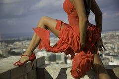 Il rosso sexy ha vestito il torso del corpo della donna sopra la città Fotografie Stock