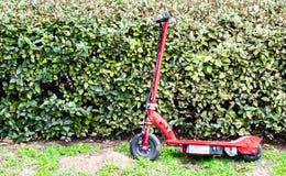 Il rosso trascurato ha motorizzato il motorino che pende contro le barriere verdi fotografie stock