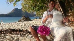 il rotolo della sposa e dello sposo sulla corda oscilla sulla spiaggia dell'isola archivi video