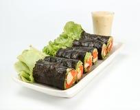 Il rotolo di molla di verdura fresca, insalata arriva a fiumi il tubo dell'alga sul piatto ceramico, alimento pulito fotografia stock